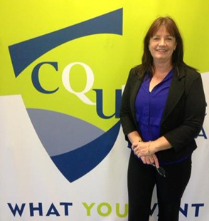 Alison Murdoch standing in front of a CQUniversity wall sign