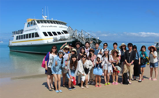 Students of Meikai University in front of a ship on the beach of Great Keppel Island