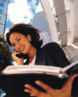 Business woman holding a binder whilst talking on the phone