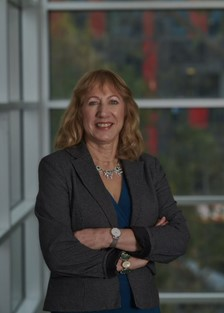 Prof Santina Bertone standing in an office crossing her arms and smiling