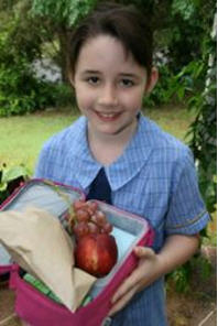 Young student holding lunchbox with healthy options including fruit