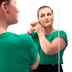 Girl putting on ear rings in front of a mirror
