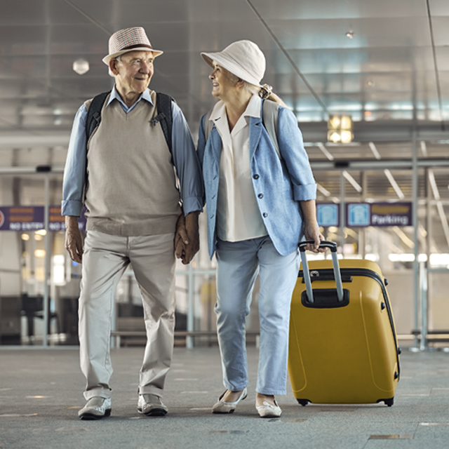 An elderly couple walking through a glass tunnel pulling suitcases