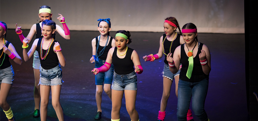 Six school aged Conservatorium Academy students dancing in black and Fluro costumes on stage