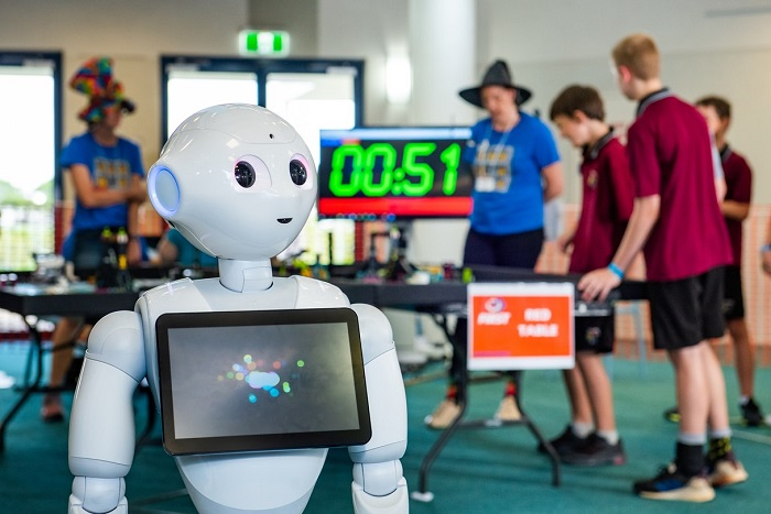 A Robot with a tablet on its chest standing in front of school students working with other robots