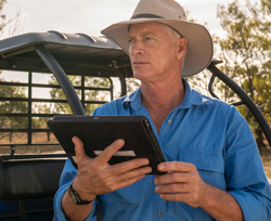 Research farmer standing in front of his quad bike holding a tablet as he looks over his farm