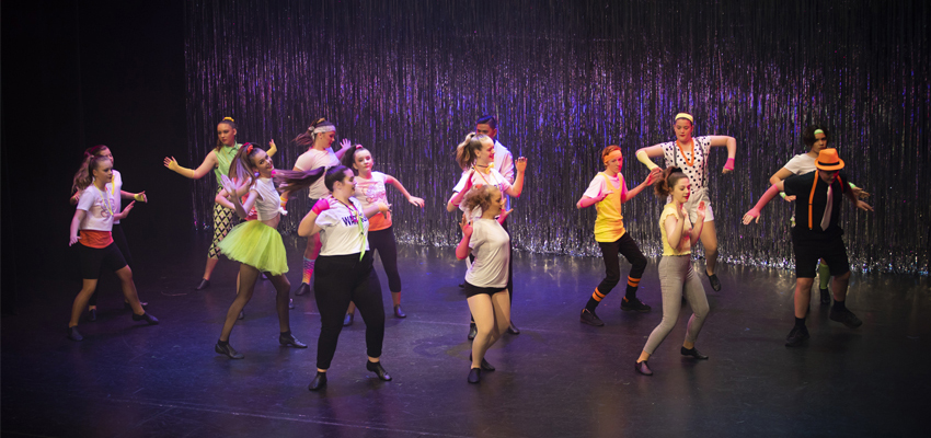 A group of high school aged Conservatorium Academy students dancing in black and Fluro costumes on stage