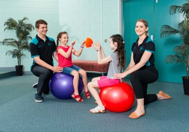 Physiotherapy students helping align two children on yoga balls as they play catch