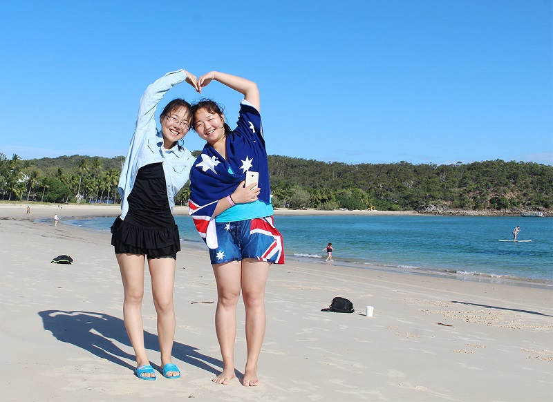 Two international students standing on Great Keppel Island beach making a heart with their arms