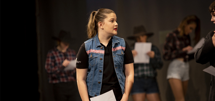 Teenage Conservatorium Academy student holding a script whilst looking over to another student off stage