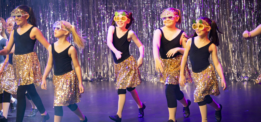 Five school aged Conservatorium Academy students dancing in sparkling costumes and sunglasses on stage